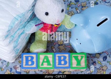 Wooden blocks spell baby, blue piggy bank, bunny toy, and diapers sit on a baby blanket - Stock Photo