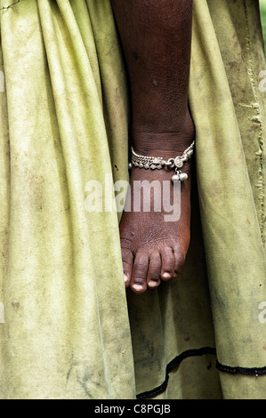 Poor Indian babies foot with ankle bracelet against mothers dirty dress abstract - Stock Photo
