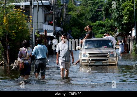 Bangkok residents wade through flood water from the overflowing Phra Khanong Canal, Sukhumvit Road, soi 50, Bangkok, - Stock Photo