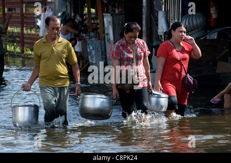 Bangkok residents carry food in metal pots, one women talks on a cel phone, through flood water from the overflowing - Stock Photo