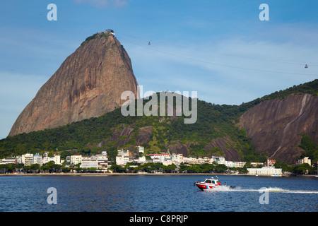 Morro da Urca and Pao de Acucar (Sugarloaf Mountain) with a boat, Rio de Janeiro, Brazil - Stock Photo