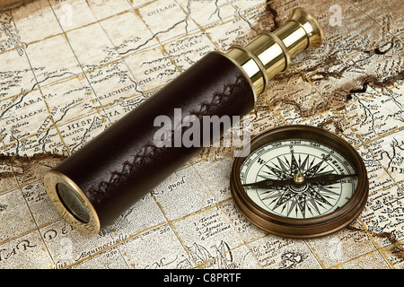 Vintage brass telescope and compass over antique map - Stock Photo