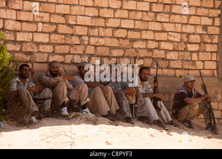Rebel relax after a hard days fighting on the road to tripoli - Stock Photo