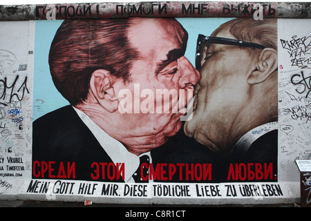 Leonid Brezhnev and Erich Honecker's kiss pictured on the Berlin Wall in East Side Gallery in Berlin, Germany. - Stock Photo