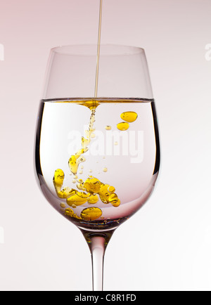Olive oil being poured into a large wine goblet forming golden bubbles in the liquid - Stock Photo