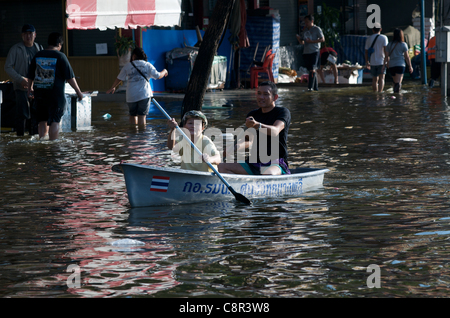 Paddling, Bangkok residents paddle boat through flood water on Phahon Yothin Road, Bangkok, Thailand, South East - Stock Photo