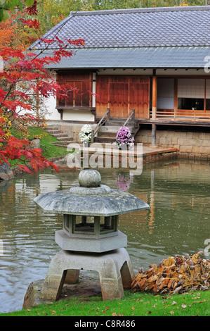 Stone lantern and pavilion / tea house in Japanese garden with tree foliage in red autumn colours in the city Hasselt, Belgium