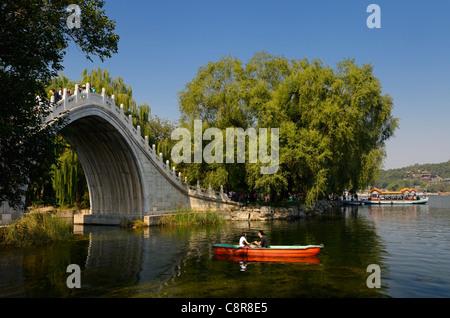 Couple rowing under the Jade Belt Bridge on Kunming Lake Summer Palace Beijing Peoples Republic of China - Stock Photo
