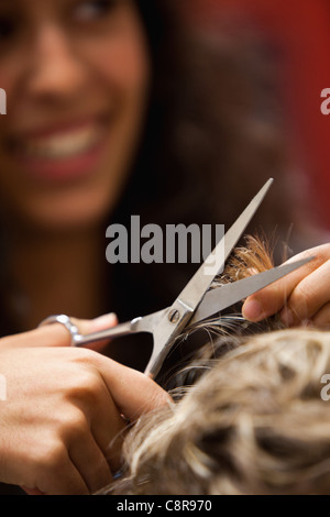Portrait of a hairdresser cutting hair - Stock Photo