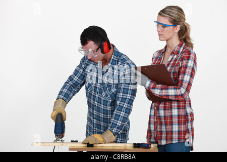 Man using band saw whilst woman supervises - Stock Photo