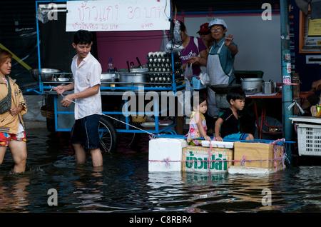 Thai father pulls his children through flood waters on a makeshift raft. Phahon Yothin Road, Bangkok, Thailand on - Stock Photo