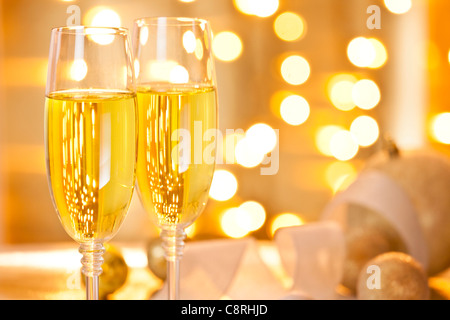 Close-up photograph of two glasses of champagne set on a table decorated with christmas ornaments - Stock Photo
