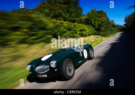 A man drives a vintage Austin Healey sports car along a country road in Hampshire, England - Stock Photo