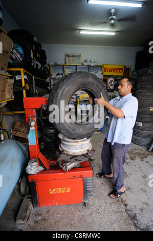 Africa, Tunisia, Nabeul. Local tunisian mechanic while repairing a tyre puncture on a Michelin XS sand tyre. - Stock Photo