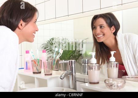 Woman looking in bathroom mirror - Stock Photo