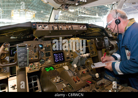 technician carrying out checks on Boeing 757 flight-deck - Stock Photo