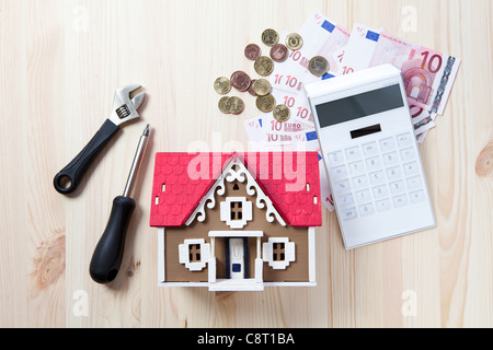 Top view of model home surrounded with calculator, money and tools - Stock Photo