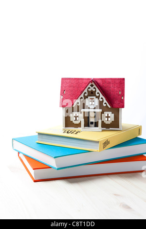 Model house placed on stack of books against white background - Stock Photo