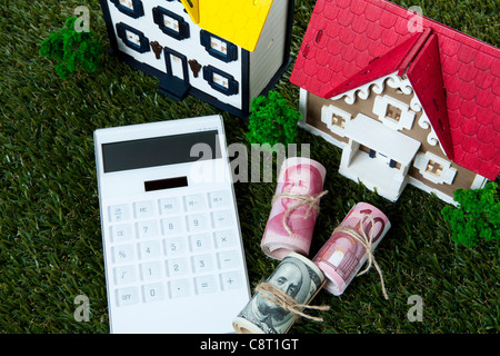 Model houses with rolled up currency notes and calculator on grass - Stock Photo