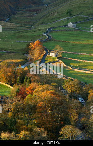 The first rays of sunlight hit the brightly colored autumn foliage of Arncliffe in Littondale, Yorkshire - Stock Photo
