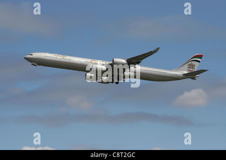 Etihad Airways Airbus A340-600 long haul airliner climbing on departure - Stock Photo