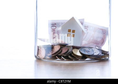 Close up of European union currency and model home in glass jar - Stock Photo