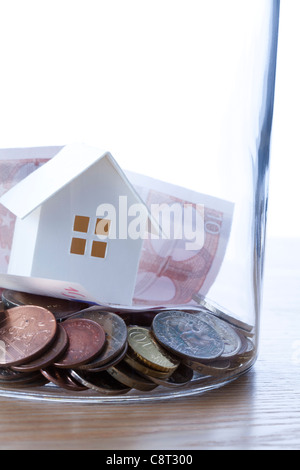 Close up of European union currency and model home in glass jar against white background - Stock Photo
