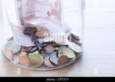 Close-up of European union currency and key in glass jar - Stock Photo