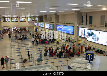 Passengers waiting to check in at Malta International Airport - Stock Photo