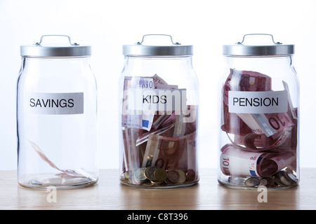 Three glass jar with label filled with money - Stock Photo