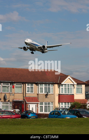 ANA Boeing 777-300ER overflying a residential area on final approach to Heathrow Airport - Stock Photo
