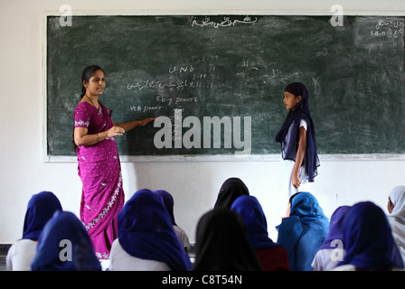 Muslim Indian girl with teacher at school Andhra Pradesh South India - Stock Photo