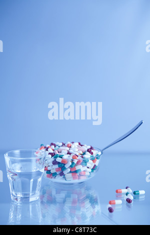 Bowl full of pills along with glass of water - Stock Photo