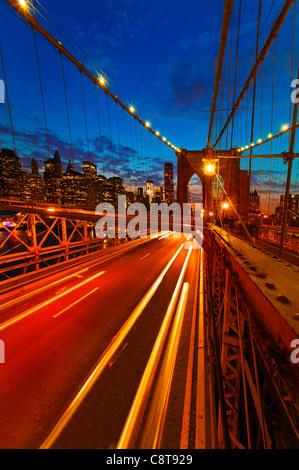 USA, New York City, Brooklyn Bridge with light trails at dusk - Stock Photo