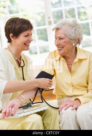 Home care nurse taking senior mans blood pressure Stock Photo