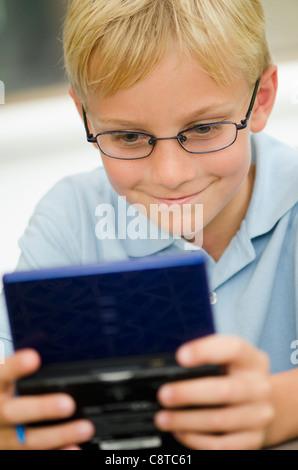 USA, New York State, Old Westbury, Boy playing video game - Stock Photo
