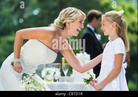 USA, New York State, Old Westbury, Bride with flower girl at wedding reception - Stock Photo