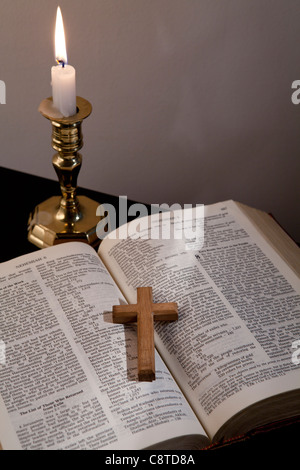 High angle view of cross lying on holy bible
