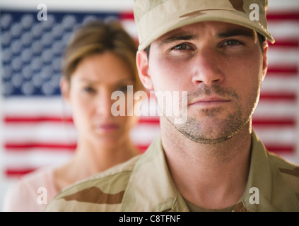 USA, New Jersey, Jersey City, Close up of soldier and his girlfriend with american flag in background - Stock Photo