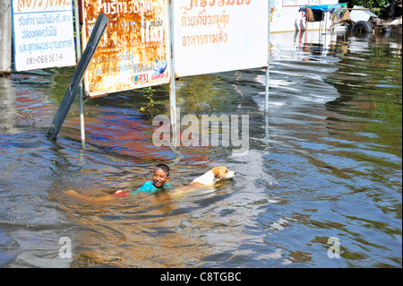Thai child swimming with his dog in floodwater during the severe floods in Thailand in 2011 - Stock Photo