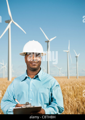 USA, Oregon, Wasco, Engineer standing in wheat field in front of wind turbines - Stock Photo