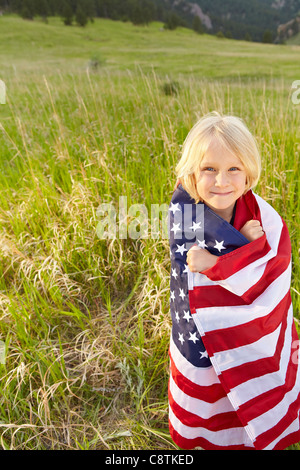USA, Colorado, Boulder, Portrait of boy wrapped in American flag - Stock Photo