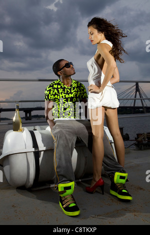 couple of lovers in harbour at night, afro-american man and caucasian woman - Stock Photo