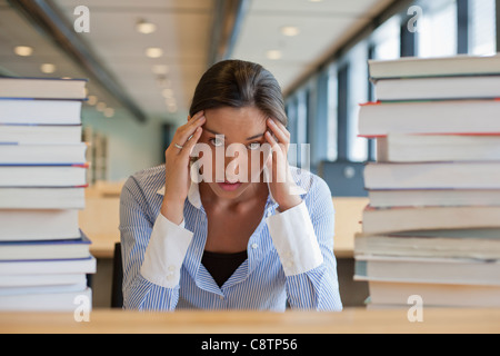Netherlands, Maastricht, Female student between stacks of books - Stock Photo