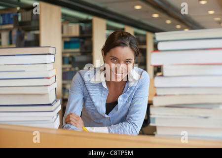 Netherlands, Maastricht, Portrait of female student between stacks of books - Stock Photo