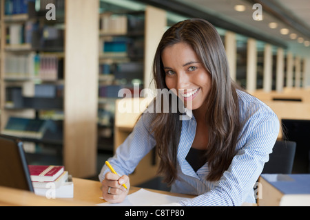 Netherlands, Maastricht, Portrait of female student studying in library - Stock Photo