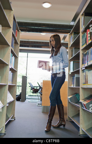Netherlands, Maastricht, Female student searching for books in library - Stock Photo