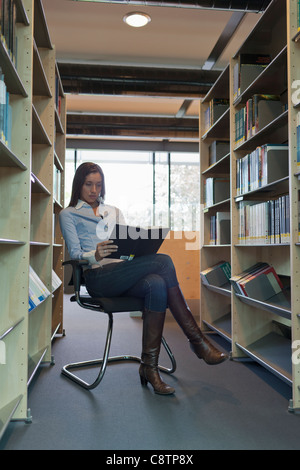 Netherlands, Maastricht, Female student studying in library - Stock Photo