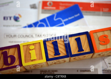 pile of bills with the word bills spelled out in building blocks on top of them - Stock Photo