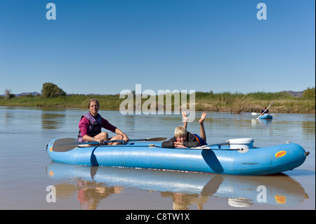 Mother and child enjoy paddling down the Oranje River at Noordoewer Namibia - Stock Photo